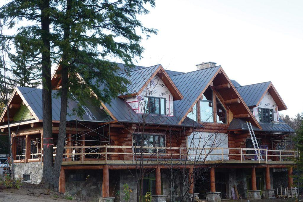 Installation d'une toiture métallique sur une majestueuse maison en bois ronds, par Toiture Corbeil